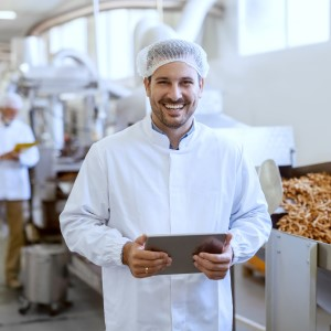 Photo of food production manager with software tablet